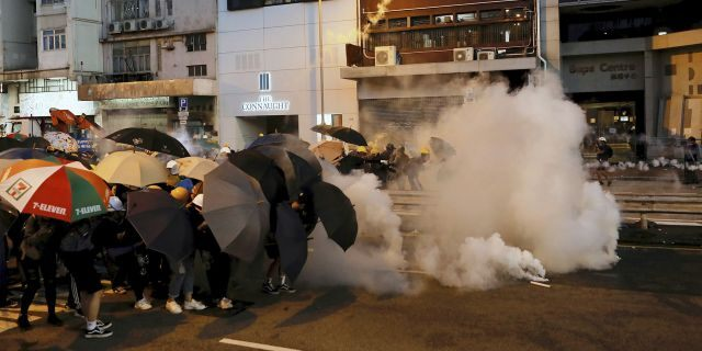Protesters use umbrellas to shield themselves from tear gas fired by policemen as they face off on a street in Hong Kong, Sunday, July 28, 2019.