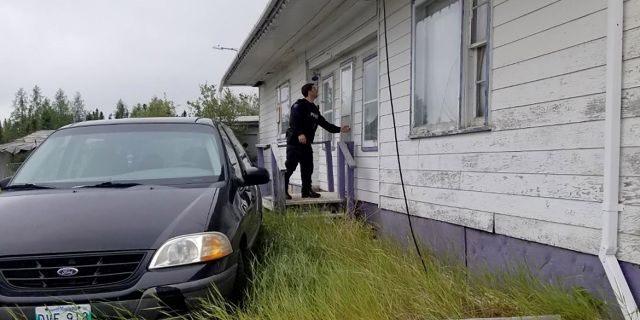 In this recent photo provided by the Royal Canadian Mounted Police, RCMP officers canvas homes and buildings in the Gillam, Manitoba area.
