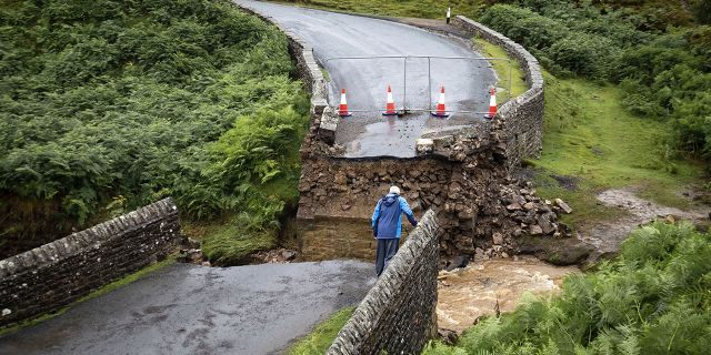 A man looks from the edge of a collapsed road bridge near Grinton, North Yorkshire, after parts of the region were inundated by overnight rain. (Danny Lawson/PA via AP)