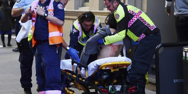 An injured woman is taken by ambulance from Hotel CBD at the corner of King and York Street in Sydney, Australia, on Tuesday, Aug. 13, 2019.