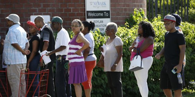 City residents line up at the Boylan Street Recreation Center with cases of bottled water, on Monday, Aug. 12, 2019, in Newark, N.J.