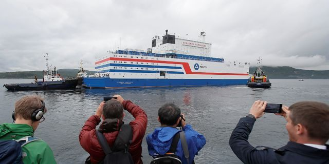 People take pictures of Russia's floating nuclear power plant Akademik Lomonosov as it leaves port Friday in Murmansk.