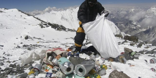 File photo - This picture taken on May 23, 2010 shows a Nepalese sherpa collecting garbage, left by climbers, at an altitude of 8,000 meters during a clean-up expedition at Mount Everest.