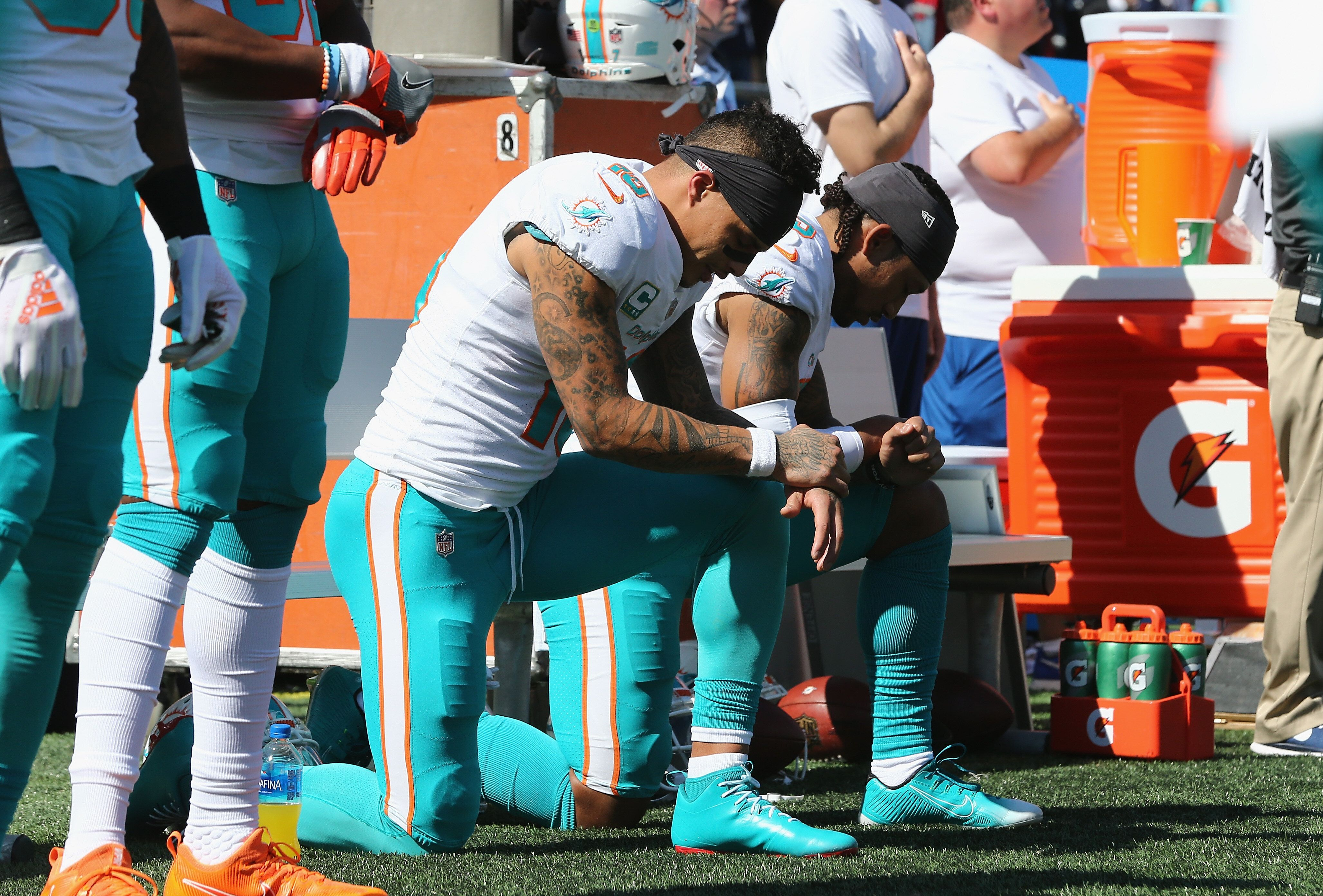Kenny Stills and Albert Wilson of the Miami Dolphins kneel during the national anthem at Gillette Stadium in Foxborough, Mass