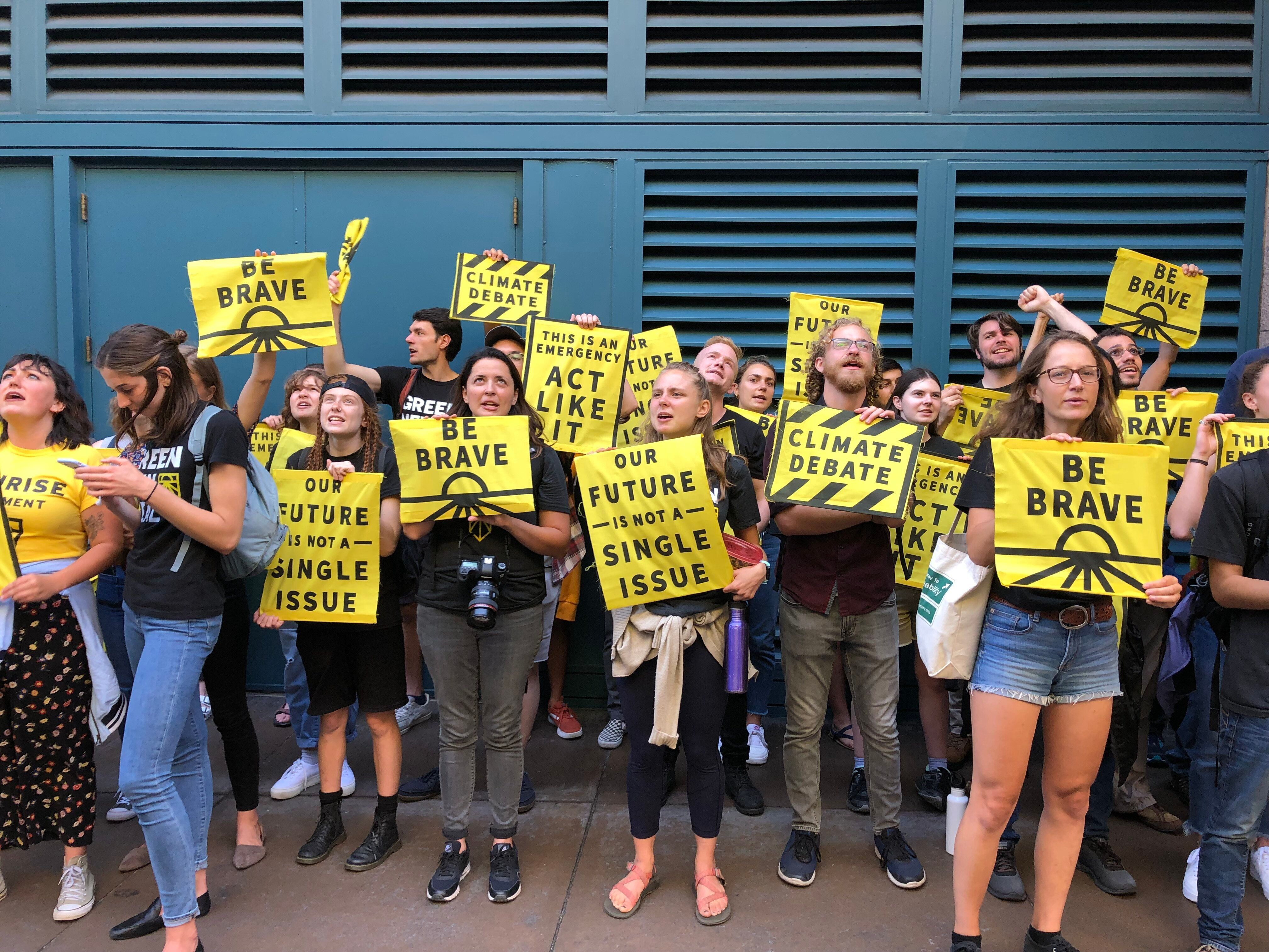 Sunrise Movement activists lobbied for a candidate debate focused solely on climate change outside the DNC's meeting Friday i