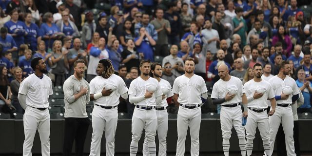 """Toronto Blue Jays players stand during the singing of the national anthem as they wear special MLB """"Players Weekend"""" jerseys before a baseball game against the Seattle Mariners, Friday, Aug. 23, 2019, in Seattle. (Associated Press)"""