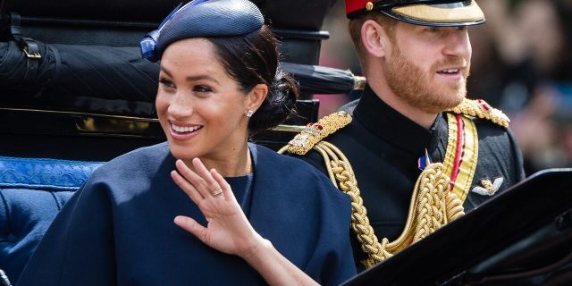 Prince Harry, Duke of Sussex and Meghan, Duchess of Sussex ride by carriage down the Mall during Trooping The Colour