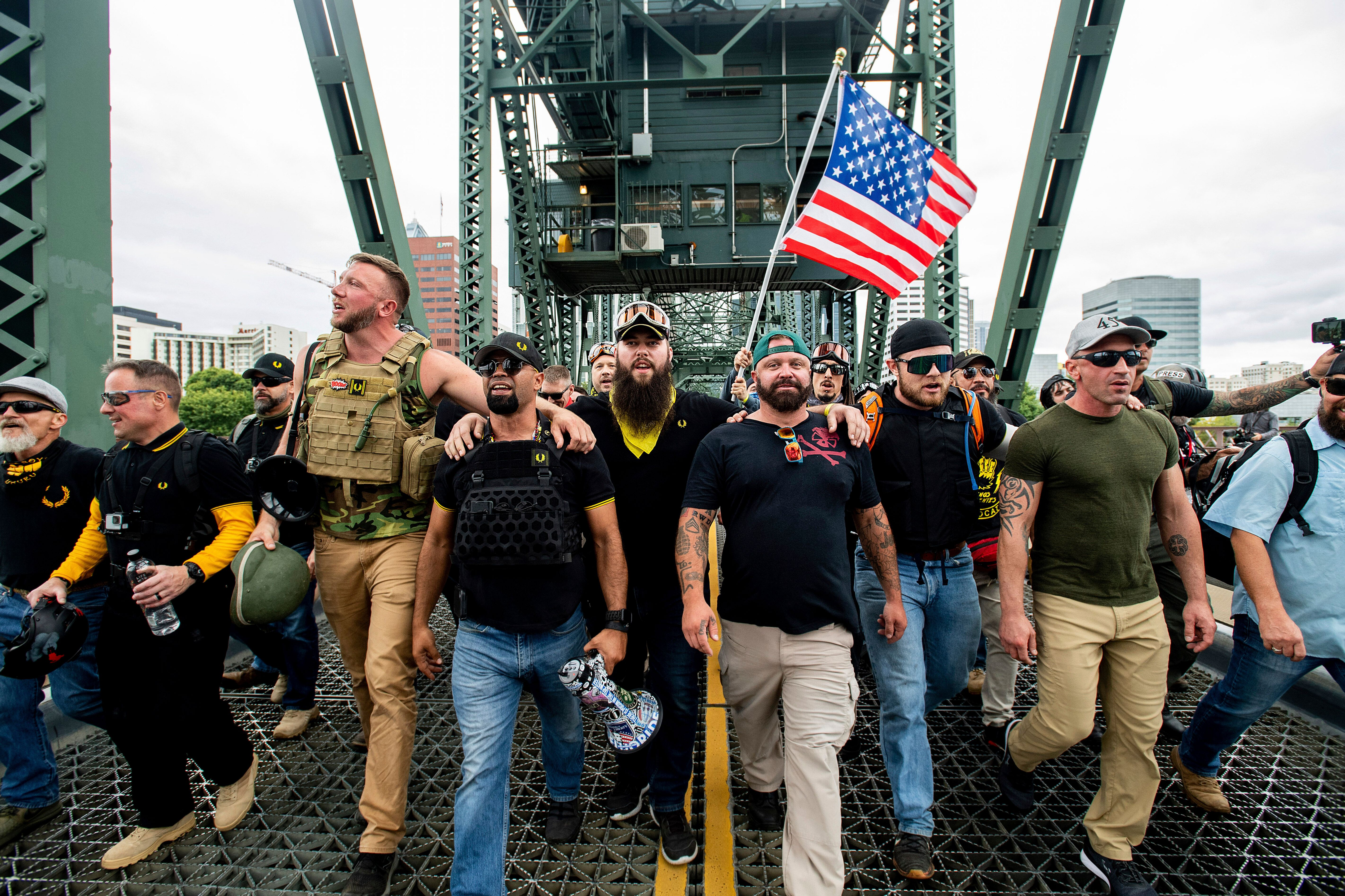 Members of the Proud Boys and other right-wing demonstrators march across the Hawthorne Bridge during a rally in Portland, Or