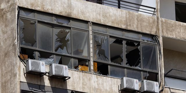 Broken windows are seen on the 11-floor building that houses the media office in a stronghold of the Lebanese Hezbollah group in a southern suburb of Beirut. (AP Photo/Bilal Hussein)