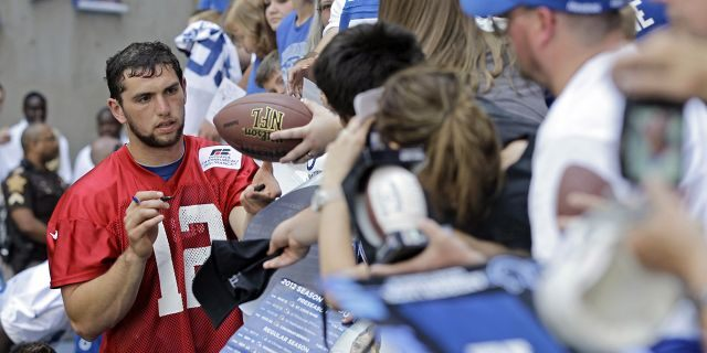 Indianapolis Colts quarterback Andrew Luck (12) signs autographs for fans following the NFL football team's practice in Indianapolis. (AP Photo/Darron Cummings, File)