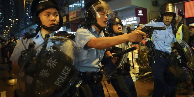Policemen pull out their guns after a confrontation with demonstrators during a protest in Hong Kong on Sundayin the outlying Tsuen Wan district.