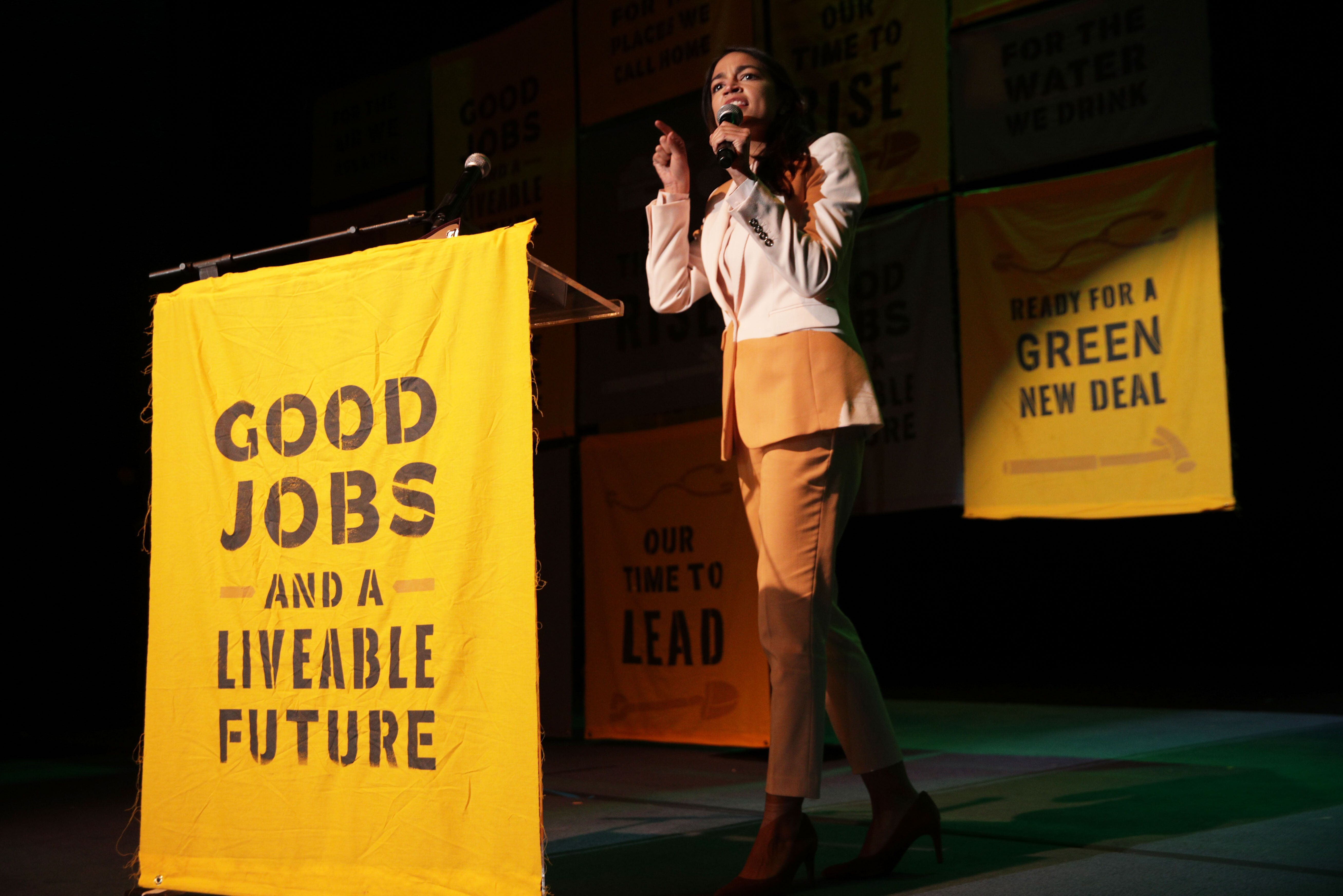 """Rep. Alexandria Ocasio-Cortez (D-N.Y.) speaks at a Green New Deal rally in May, calling for """"good jobs"""" and a safe climate.&n"""
