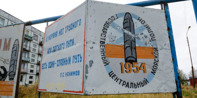 """This photo taken on Oct. 7, 2018, shows a billboard that reads """"The State Central Navy Testing Range"""" near residential buildings in the village of Nyonoksa, northwestern Russia."""
