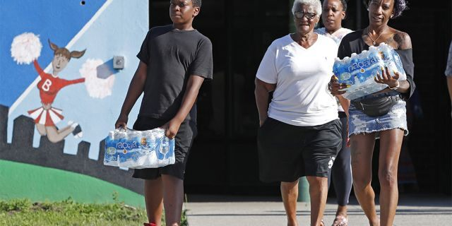 Rahjiah McBride, of Chester, Pa., right, helping her relatives, Newark residents Elnora and Bowdell Goodwin, center and second right, as Goodwin's son pitches in carrying bottled water earlier this month. (AP Photo/Kathy Willens)