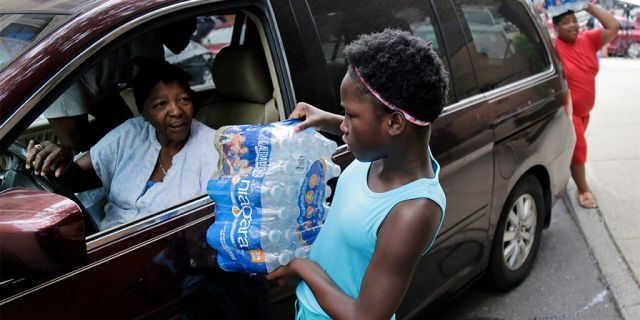Elaine Younger, 11, and Tahvion Williams, 14, right, loading water in their family's van at the Newark Health Department earlier this month. (AP Photo/Seth Wenig)