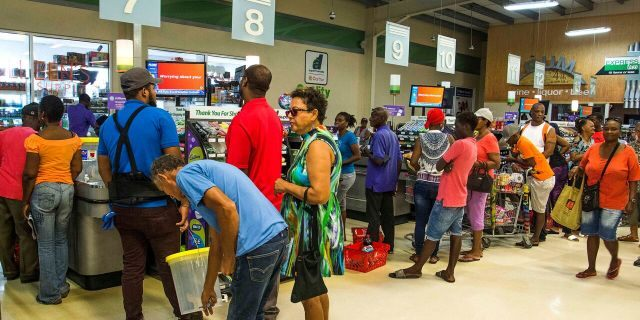 Residents stand in line at a grocery store as they prepare for the arrival of Tropical Storm Dorian, in Bridgetown, Barbados, Monday, Aug. 26, 2019.