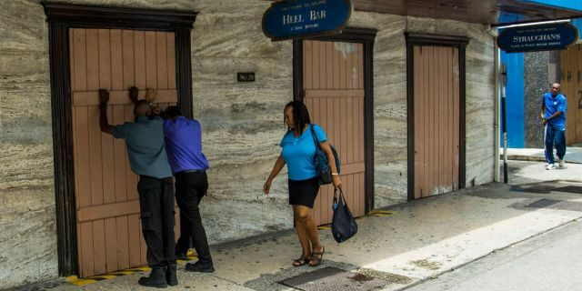 Residents board up a storefront pharmacy as they prepare for the arrival of Tropical Storm Dorian, in Bridgetown, Barbados, Monday, Aug. 26, 2019.