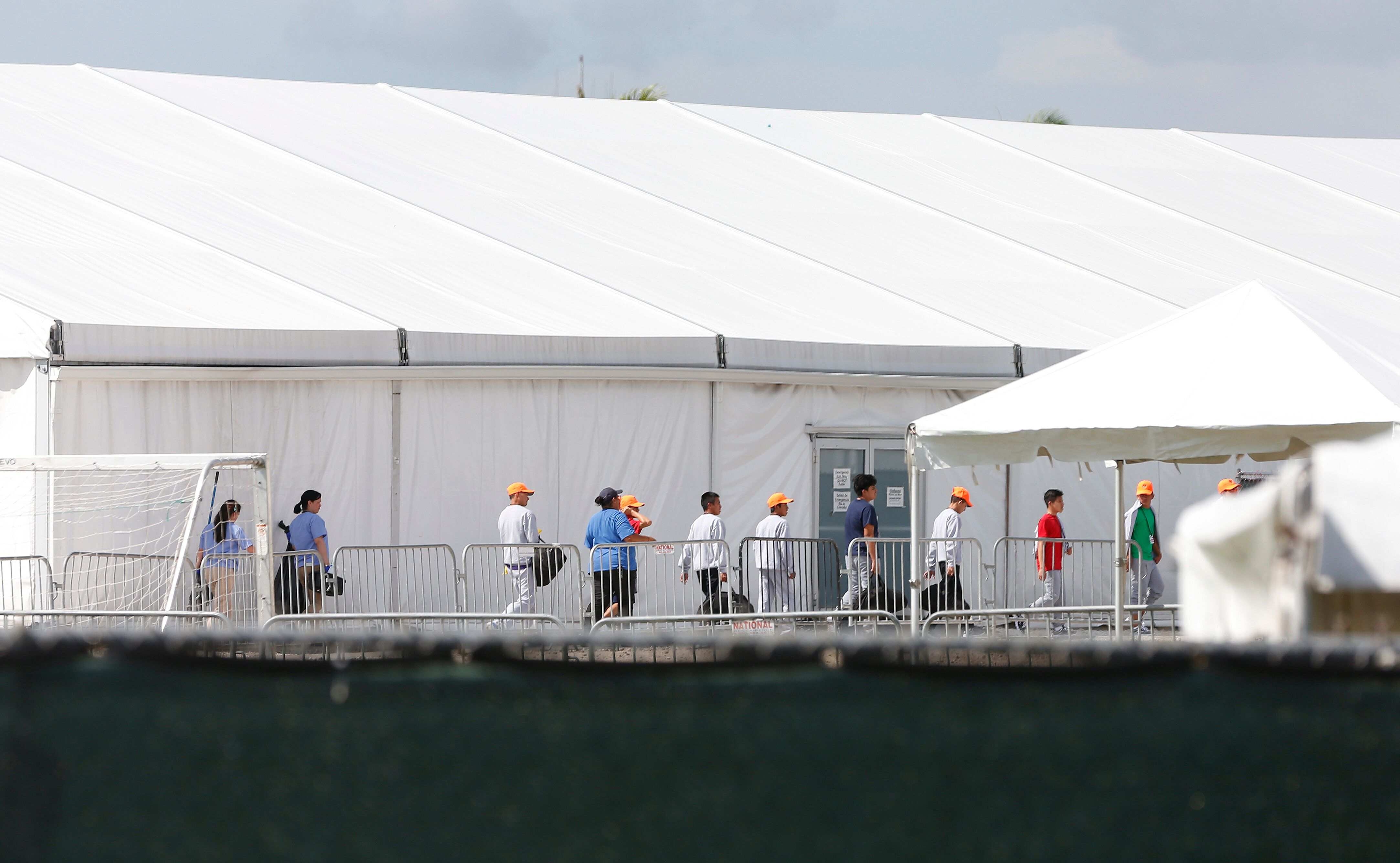 Migrant children separated from their families walk past tents at a detention center in Homestead, Florida on June 27, 2019.