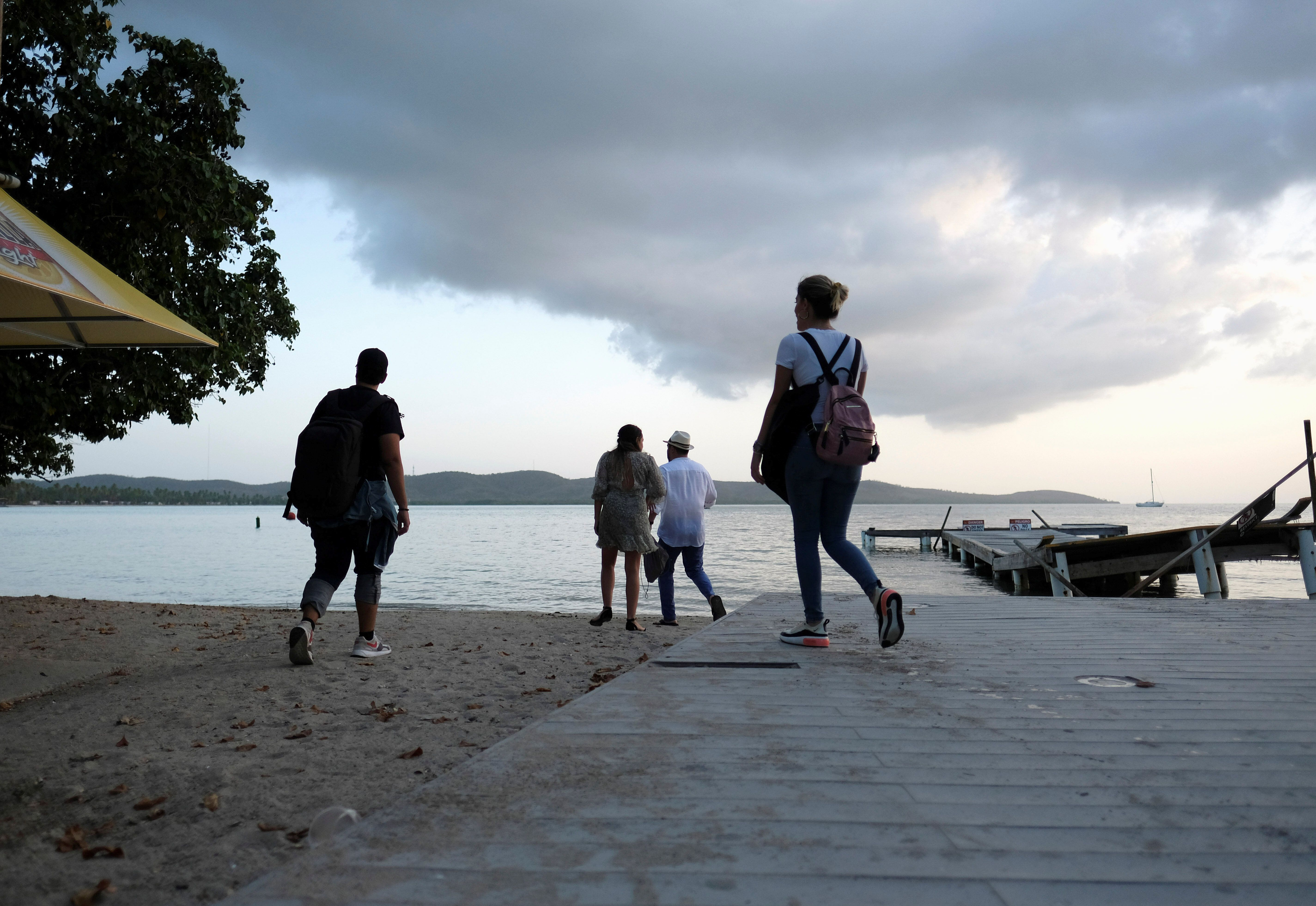 A group of people walk on the beach in the tourist zone of Boquerón as Tropical Storm Dorian approaches on Aug. 26, 20