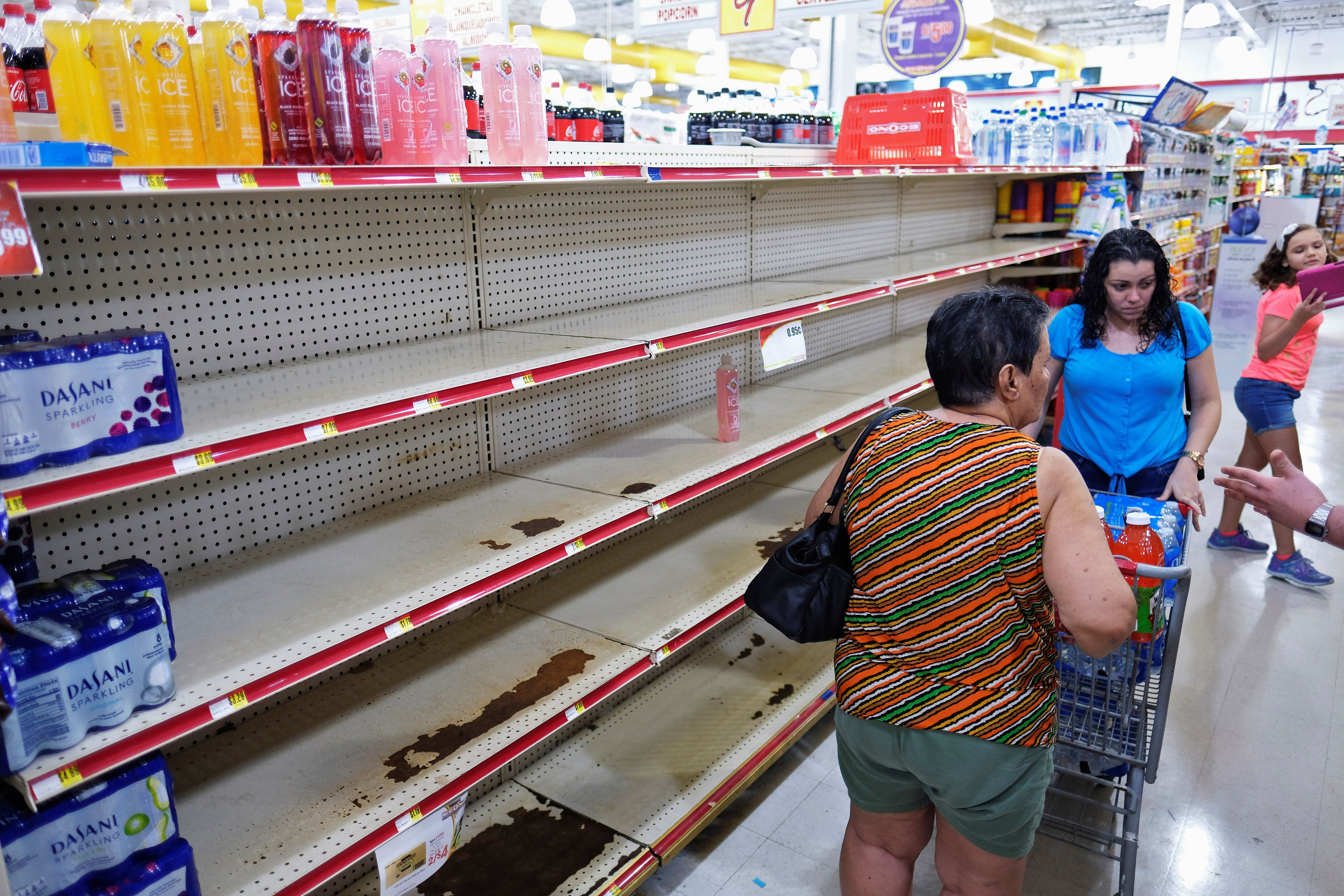 Nearly empty shelves where bottled water is normally displayed at a grocery store in Cabo Rojo, Puerto Rico, as Tropical Stor
