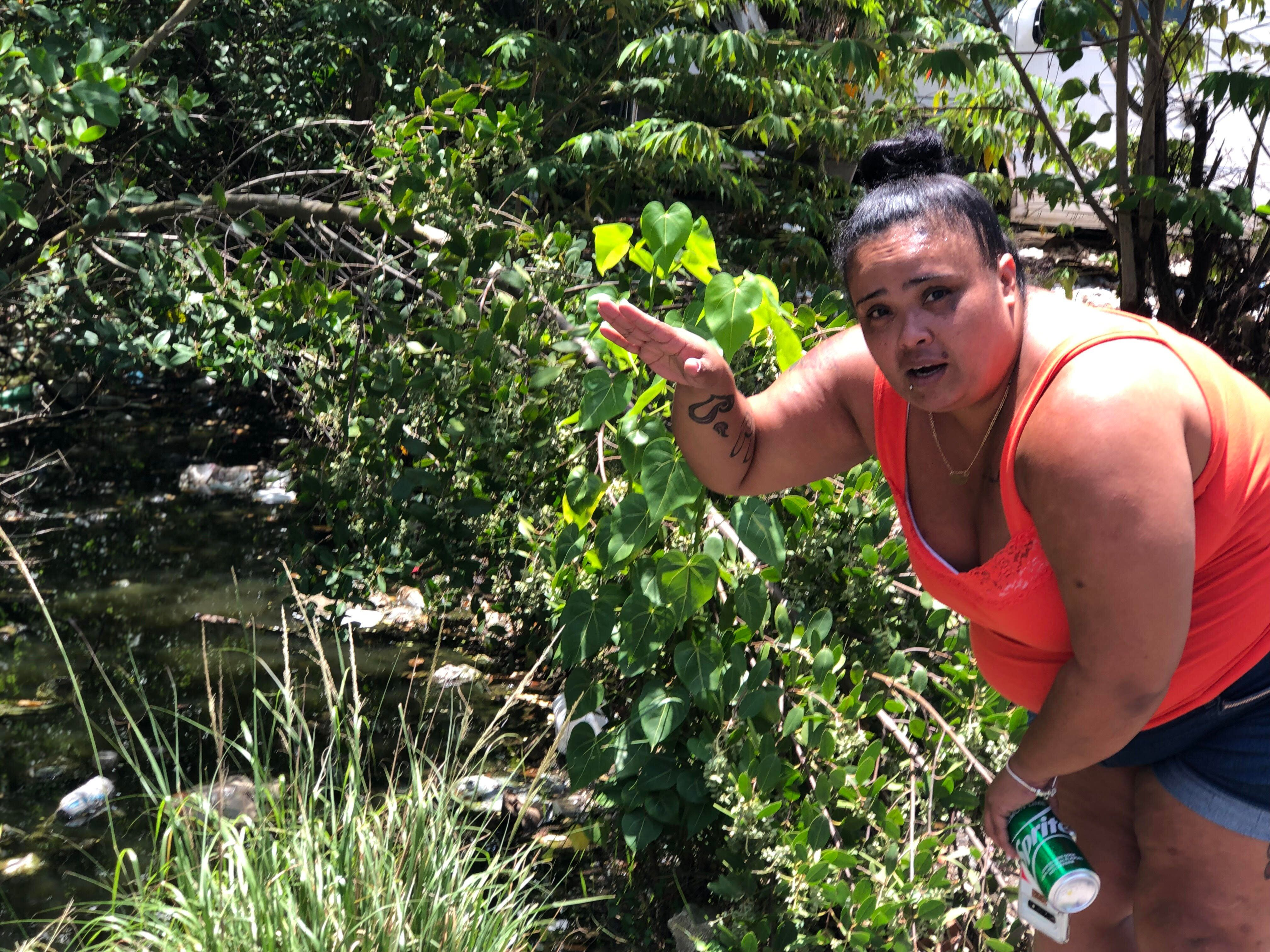 Milagros Figueroa gestures next to Caño Martín Peña, a nearly four-mile polluted canal that she said flo