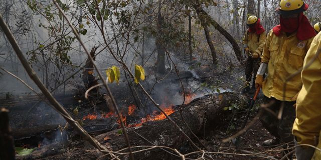 Soldiers work to put out a forest fire in the Chiquitania Forest of Quitunuquina near the Robore, Bolivia, Monday, Aug. 26, 2019.