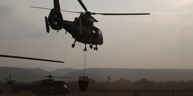 A helicopter lifts off from a military airport Robore, Bolivia, with water to drop on the Chiquitanía Forest as the military fights forest fires, Sunday, Aug. 25, 2019.