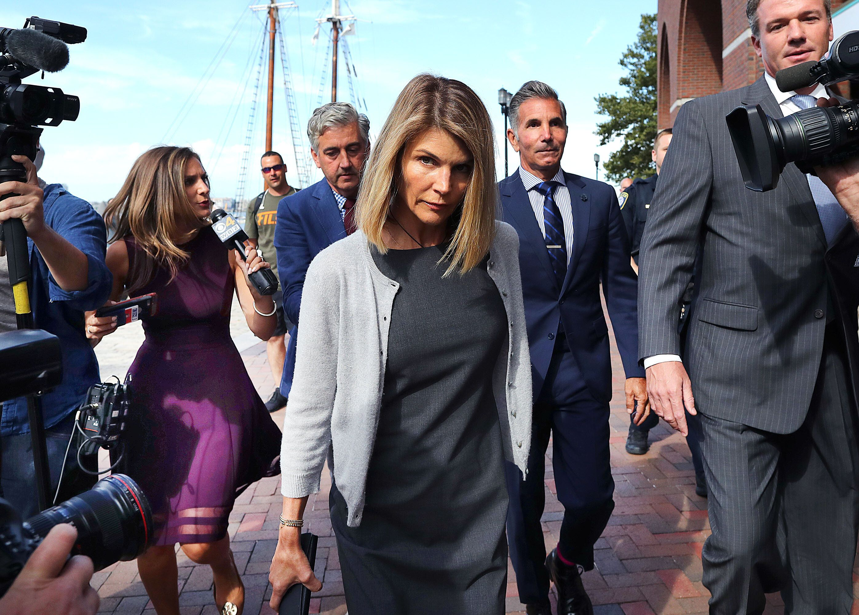 BOSTON, MA - AUGUST 27: Lori Loughlin, center, and her husband Mossimo Giannulli, behind her at right, leave the John Joseph