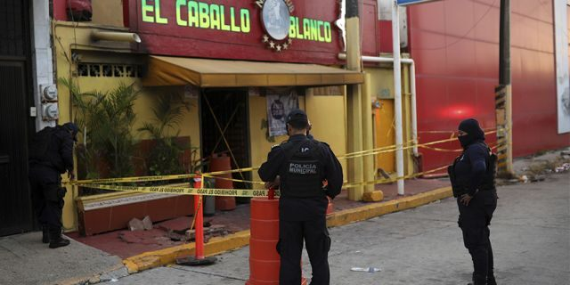 Police officers guard the scene outside a bar where more than 20 people died in an overnight attack, in Coatzacoalcos, Mexico, on Wednesday.
