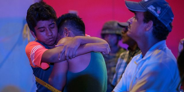 A man is comforted at a crime scene following a deadly attack at a bar by unknown assailants in Coatzacoalcos, Mexico, on Wednesday.