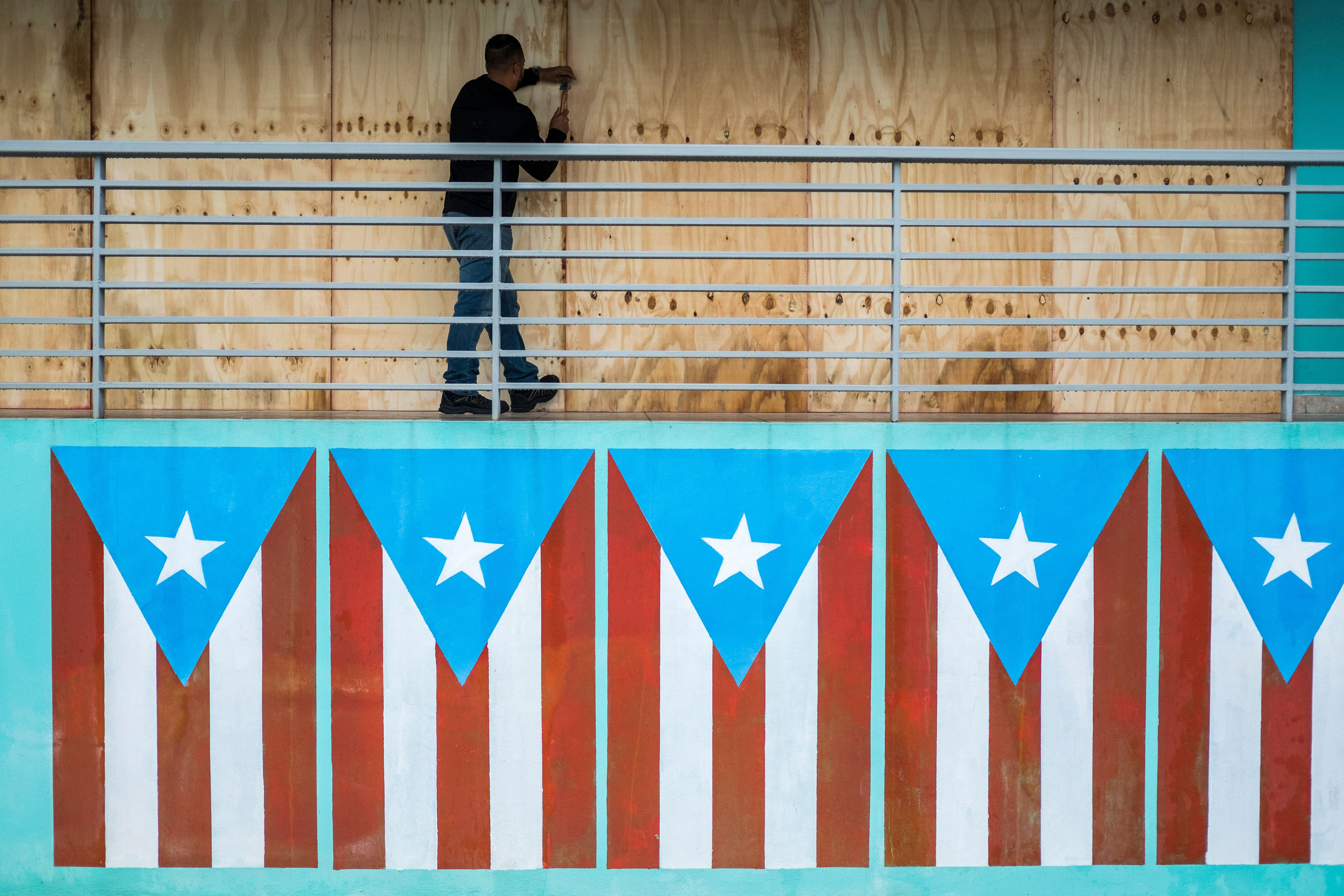 A man finishes boarding up a restaurant at the Naguabo Malecon in Naguabo, Puerto Rico, on Wednesday.