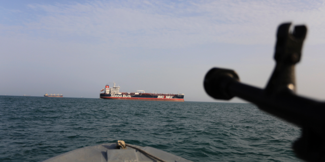 A speedboat belonging to Iran's Revolutionary Guard Corps trains a weapon toward the British-flagged oil tanker Stena Impero, which was seized in the Strait of Hormuz on July 19. (AP/Tasnim News Agency)