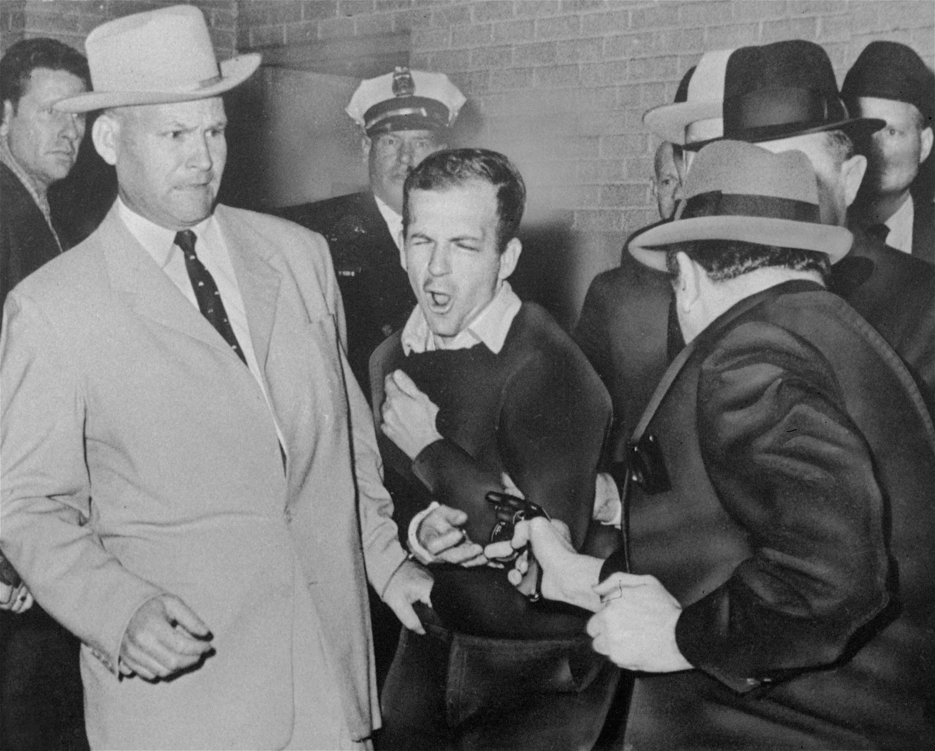 Lee Harvey Oswald, the assassin of President John F. Kennedy, reacts as Dallas night club owner Jack Ruby, foreground, shoots