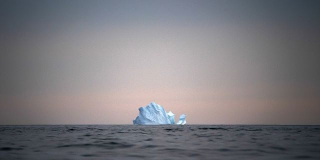 In this Aug. 15 photo, a large Iceberg floats away as the sun sets near Kulusuk, Greenland.  (AP Photo/Felipe Dana)