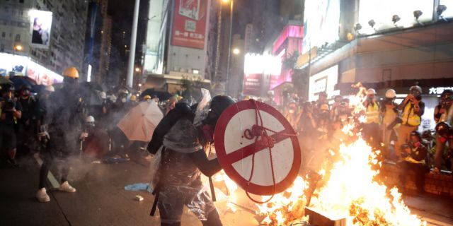 A protestor uses a shield to cover himself as he faces policemen in Hong Kong, Saturday, Aug. 31, 2019.
