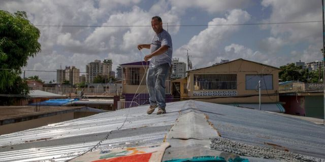 Jorge Ortiz works to tie down his roof as he prepares for the arrival of Dorian in San Juan, Puerto Rico, Tuesday, Aug. 27, 2019. (AP Photo/Gianfranco Gaglione)