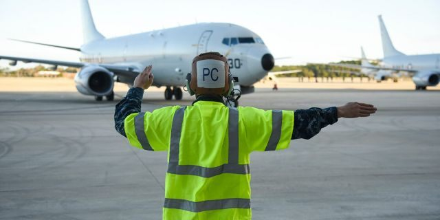 Aviation Machinist Mate 3rd Class Benjamin Harrell signals the crew of a P-8A Poseidon patrol aircraft. (U.S. Navy photo by Mass Communication Specialist 2nd Class Sean R. Morton/Released)