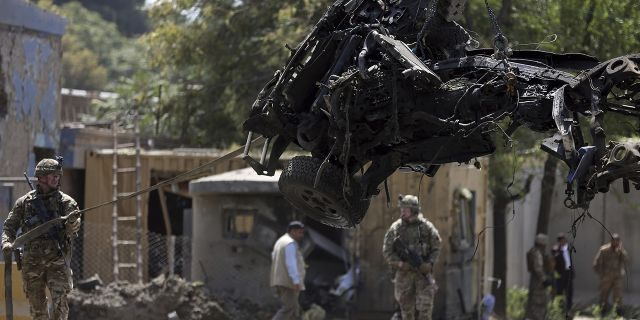 Resolute Support (RS) forces remove a damaged vehicle after a car bomb explosion in Kabul, Afghanistan, Thursday, Sept. 5, 2019. A car bomb rocked the Afghan capital on Thursday and smoke rose from a part of eastern Kabul near a neighborhood housing the U.S. Embassy, the NATO Resolute Support mission and other diplomatic missions. (AP Photo/Rahmat Gul)