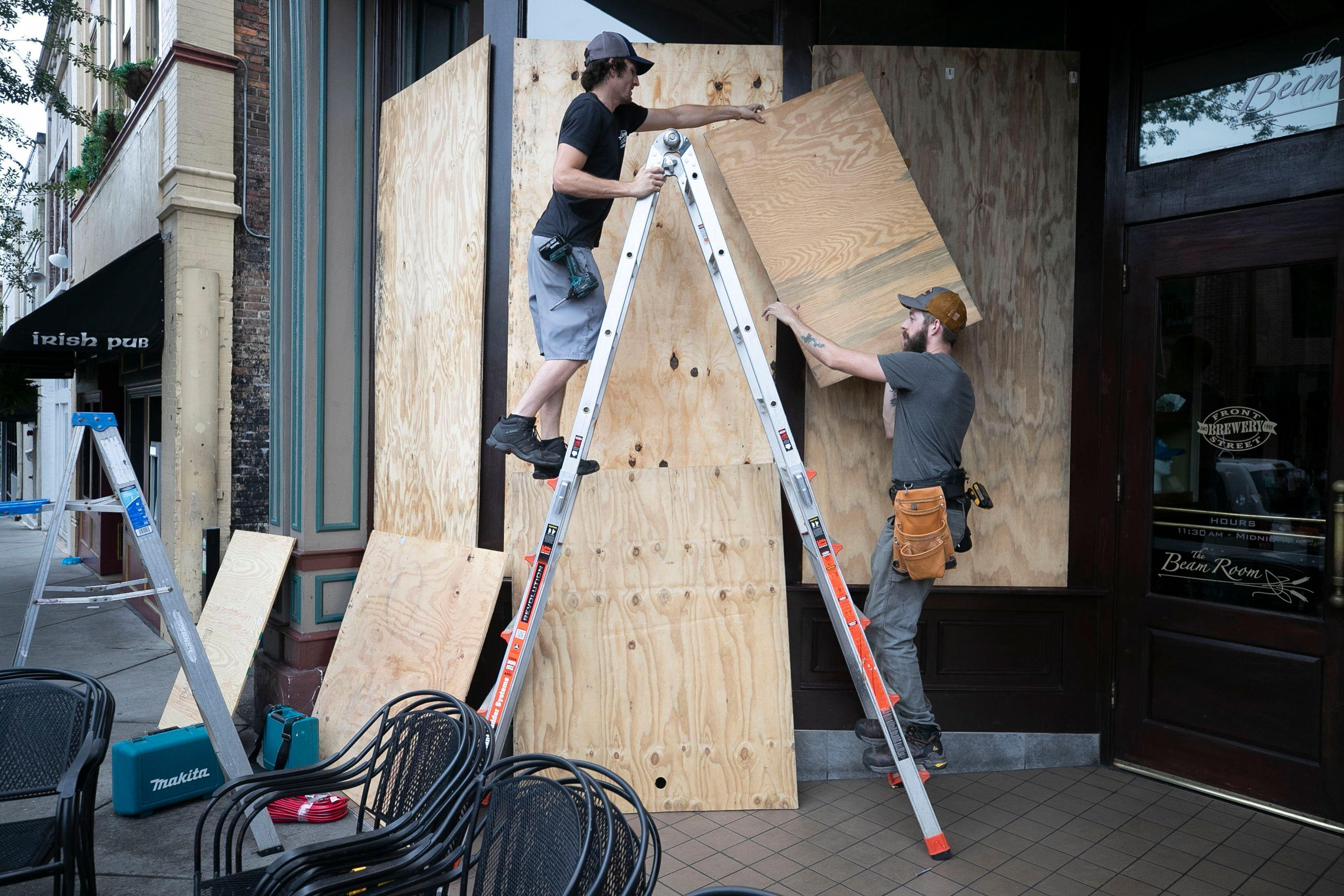 Andrew West, left and Michael Leibler install plywood over the windows of the Front Street Brewery ahead of Hurricane Dorian