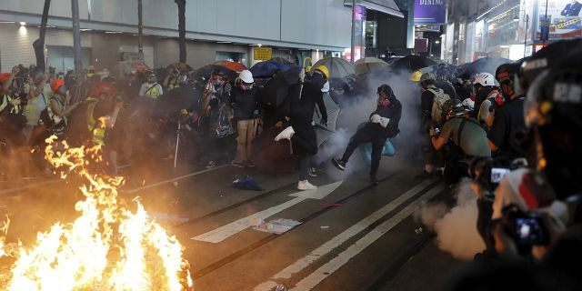 Protesters kicked back an exploded tear gas shell at police officers during a pro-democracy protest in causeway bay over the weekend. (AP Photo/Kin Cheung)