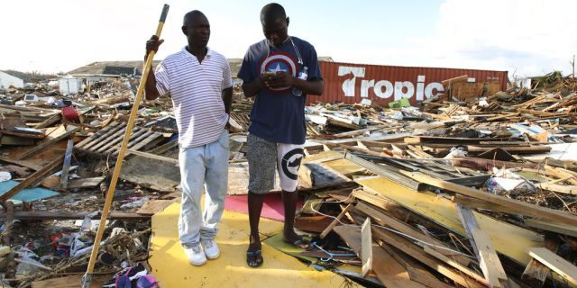 Haitian Burris Filburt, right, and another man stand on the extensive damage and destruction in the aftermath of Hurricane Dorian is seen in The Mudd, Great Abaco, Bahamas, Thursday, Sept. 5, 2019.