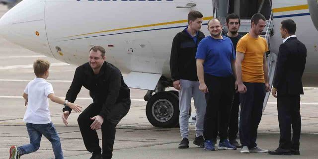 Ukraine's President Volodymyr Zelenskiy, right, greets Ukrainian prisoners upon their arrival at Boryspil airport, outside Kyiv, Ukraine, Saturday, Sept. 7, 2019.