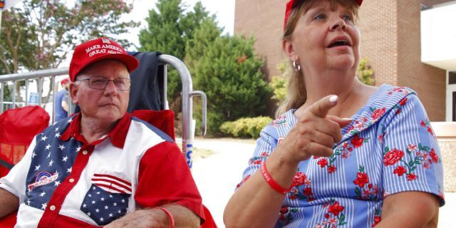 Philip Ezzell, left, and his wife, Diane Ezzell, from Marshville, N.C., talk about why they support President Trump as they wait in line to enter his latest rally on Monday. (AP Photo/Chris Seward)