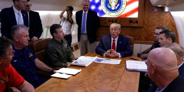 President Trump participates in a briefing with North Carolina Gov. Roy Cooper, left, and House Minority Leader Kevin McCarthy of Calif., standing center, about Hurricane Dorian at Marine Corps Air Station Cherry Point, Monday, aboard Air Force One. (AP Photo/Evan Vucci)