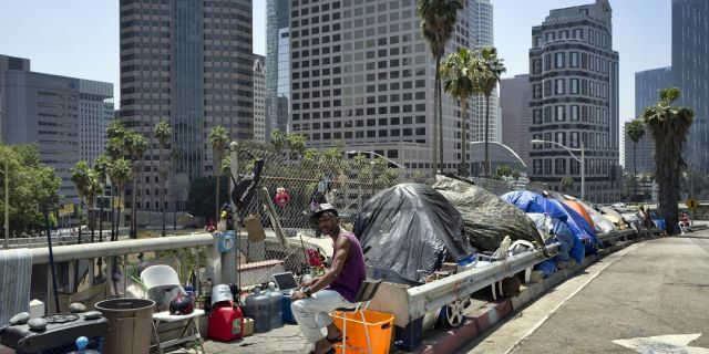 In this May 10, 2018 file photo, a homeless person sits at his tent along the Interstate 110 freeway downtown Los Angeles.