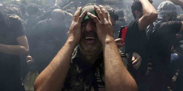 A Shiite Muslim mourns while actors re-enact the battle of Karbala in present-day Iraq in the 7th century during which Hussein, the grandson of Prophet Muhammad, and 72 of his companions were killed, in Ashoura commemoration in downtown Tehran, Iran, Tuesday, Sept. 10, 2019.