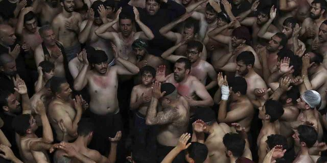 Iranian and Iraqi Shiite Muslims beat their heads during a mourning ceremony marking Ashoura in downtown Tehran, Iran, Tuesday, Sept. 10, 2019.