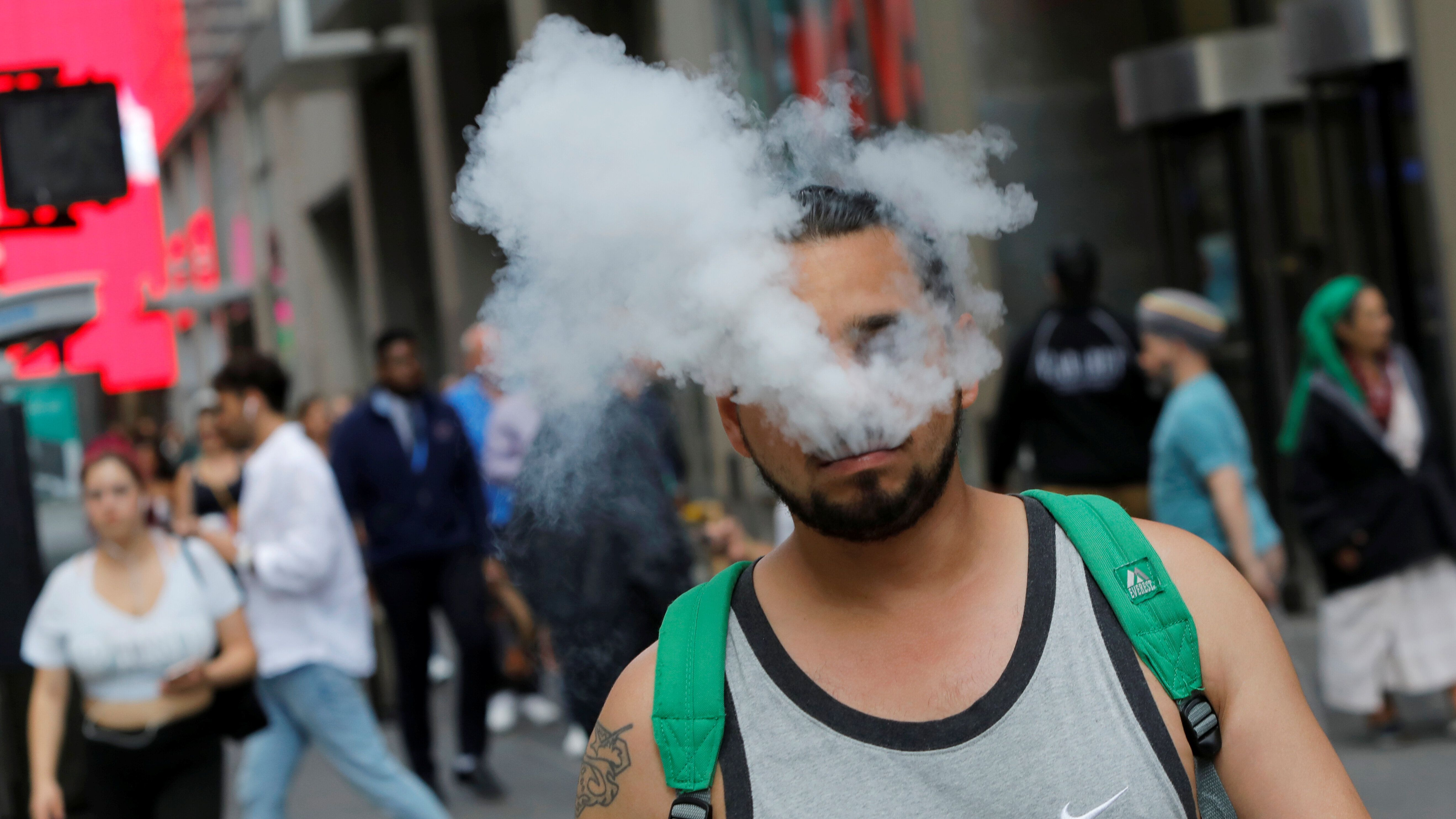 A man uses a vape as he walks on Broadway in New York City, U.S., September 9, 2019. REUTERS/Andrew Kelly
