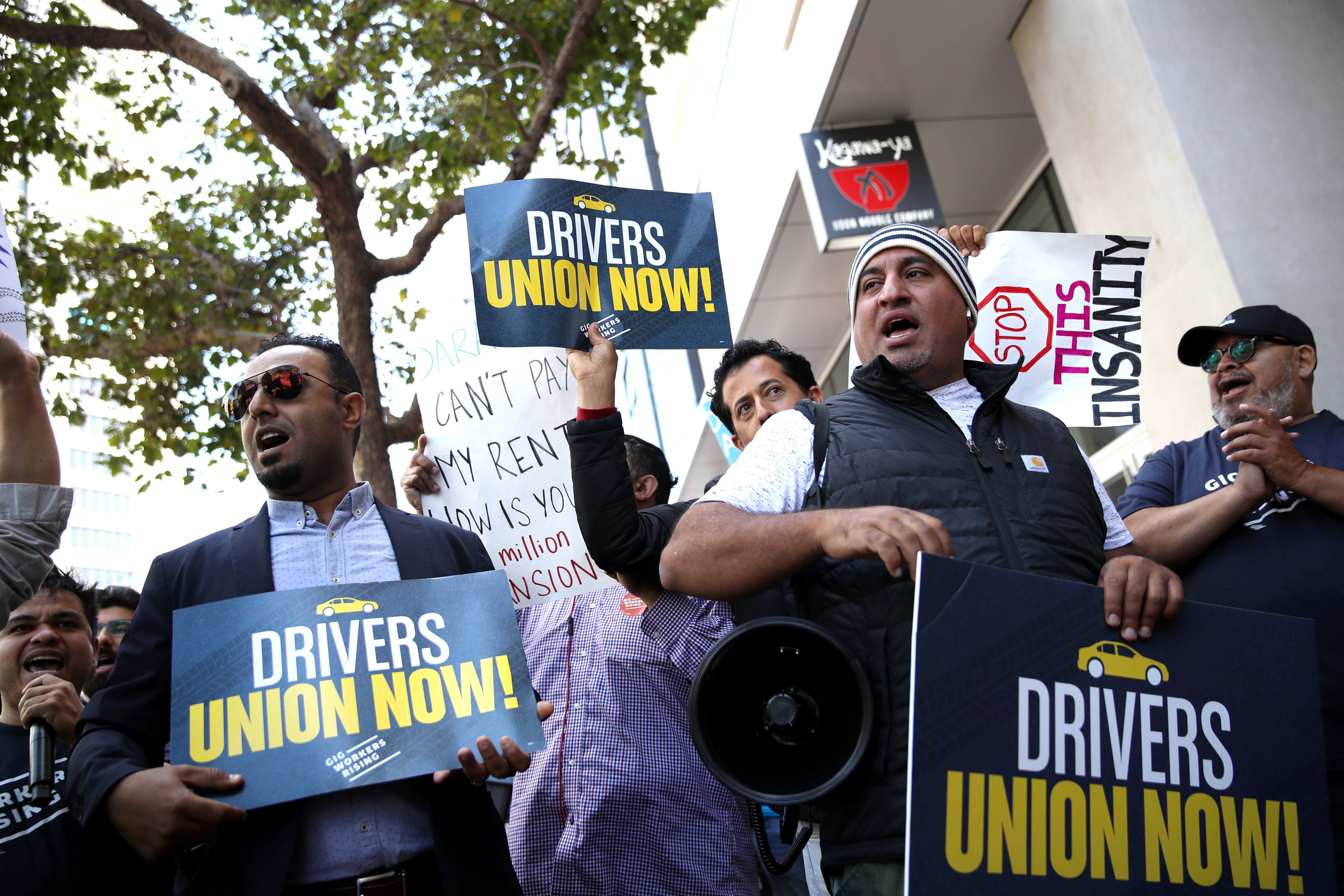 Rideshare drivers hold signs during a protest outside Uber headquarters in San Francisco in support of California labor legis