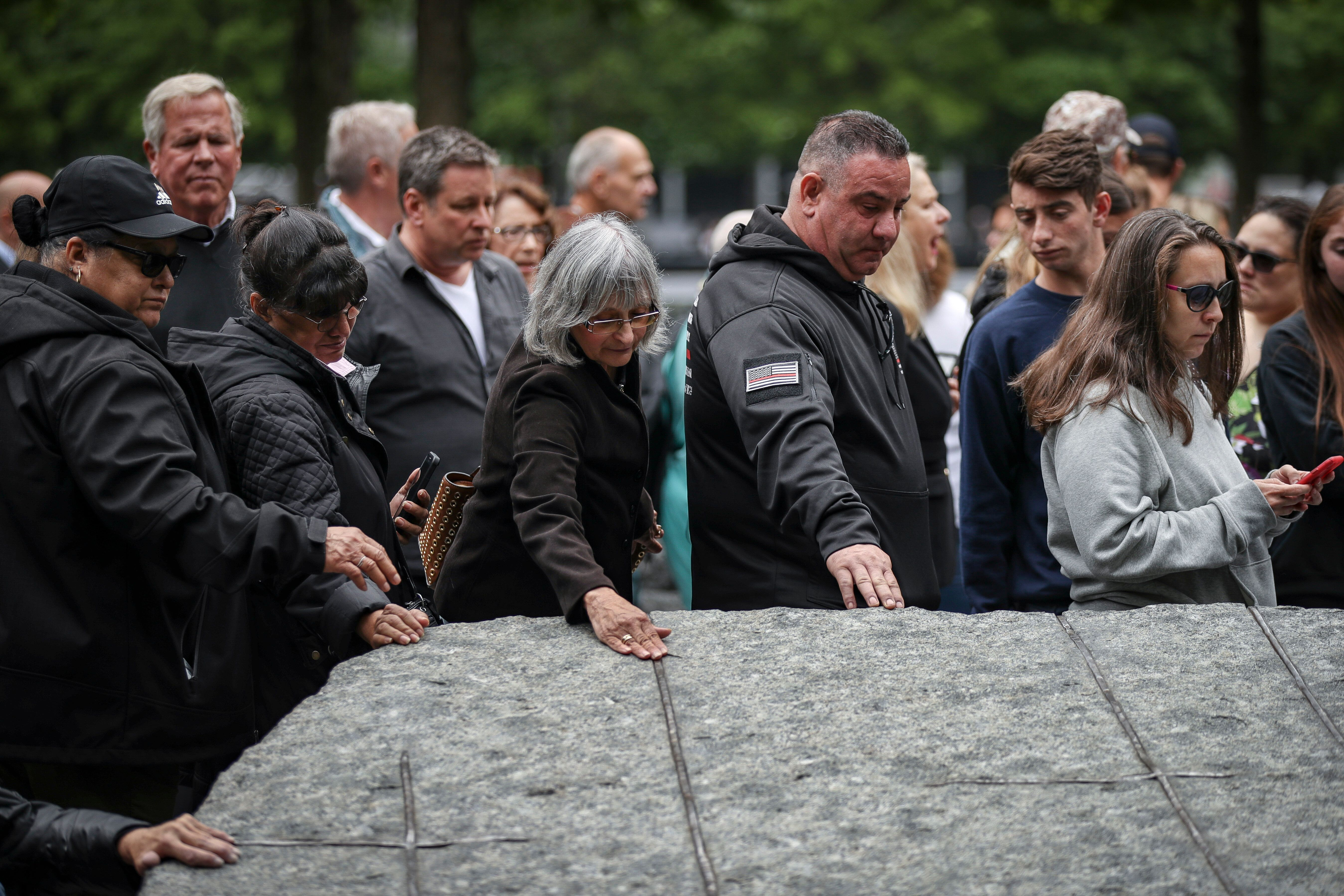 NEW YORK, NY - MAY 30: Attendees touch one of the stone monoliths following the dedication ceremony for the new 9/11 Memorial